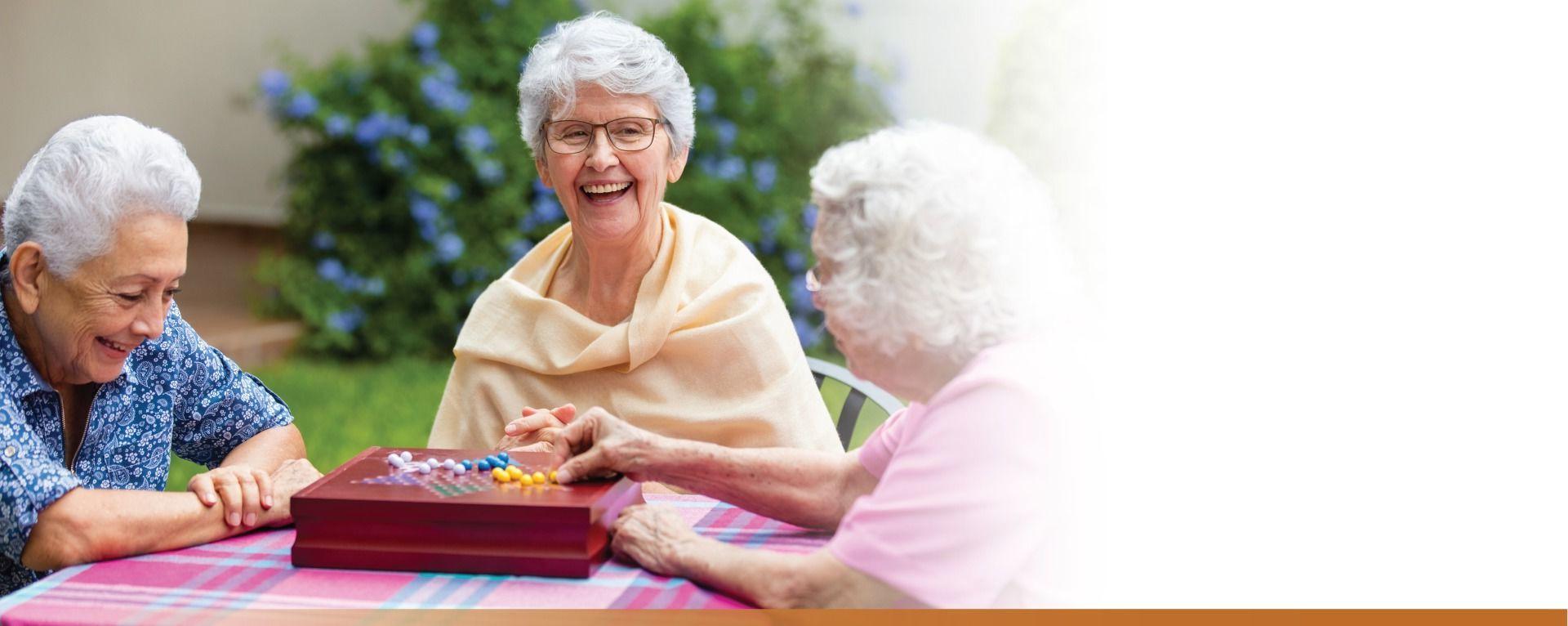 Three senior women playing Chinese checkers in patio